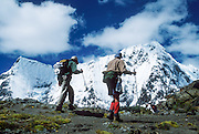 Trekkers cross a pass beneath snowy Rondoy Peak (5870 m or 19,260 feet), in the Cordillera Huayhuash, Andes Mountains, Peru, South America.