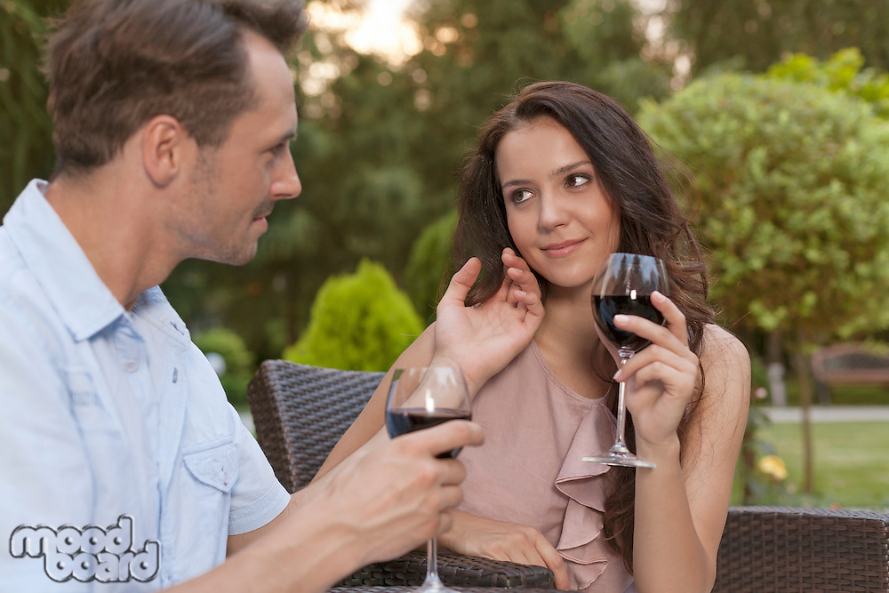Loving young couple holding wine glasses in park