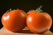 Ripe greenhouse tomato on black background