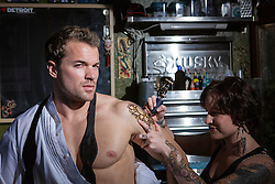 man with an open tuxedo shirt getting a tattoo in a tattoo parlor