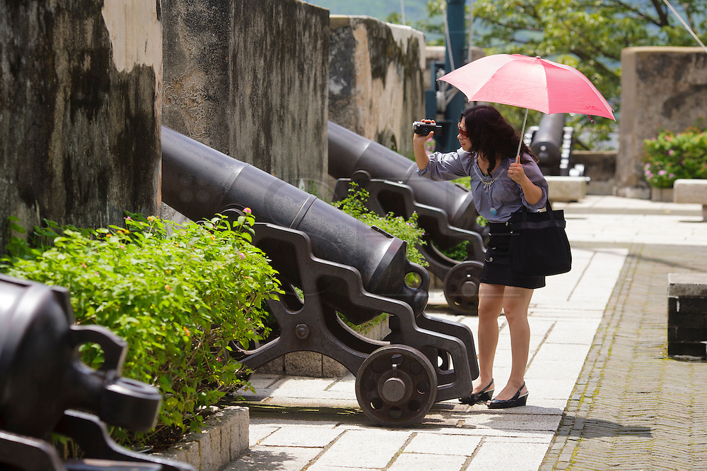 A tourist takes pictures of Macau view from the fortress (Fortaleza do Monte.
