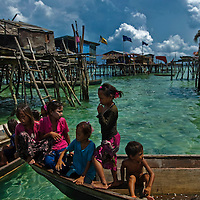 Sea Gypsies children play on a boat near their home in Celebes Sea or Sulawesi Sea off the coast of Semporna in the state of Sabah on Borneo Island. The Bajau, (also written as Badjao, Badjaw or Badjau) are an indigenous ethnic group of Malaysia and the southern Philippines. Although native to the southern Philippines, due to escalated conflicts in the Sulu Archipelago in the southern part of the country, many of the Bajau had migrated to neighboring Malaysia over the course of 50 years. Groups of Bajau had also migrated to Sulawesi and Kalimantan in Indonesia, although figures of their exact population are unknown. They were sometimes referred to as the Sea Gypsies, although the term has been used to encompass a number of non-related ethnic groups with similar traditional lifestyles, such as the Moken of the Burmese-Thai Mergui Archipelago and the Orang Laut of southeastern Sumatra and the Riau Islands of Indonesia. The modern outward spread of the Bajau from older inhabited areas seems to have been associated with the development of sea trade in trepang.