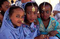 """Pakistan - """"Shiddis """", esclaves de l'empire des Indes - C'est à Mango Pir, mausolée d'un saint soufi du XIII éme siècle, situé à l'extérieur de Karachi que cette communauté noire, tiraillée entre ses racines africaines animistes et son identité musulmane pakistanaise, se retrouve et s'épanouit. Ils campent autour du mausolée dans des abris de fortune - Pendant quatre jours, des milliers de Shiddis venus de tout le sud du Pakistan, festoient, dansent, chantent, prient ensemble - Tous les jours, suivant des rites immuables venus de la nuit des temps, des groupes de Shiddis vont en dansant jusqu'au bassin aux crocodiles pour rendre hommage aux sauriens sacrés, gardiens et protégés de Mango Pir. Ici trois fillettes mènent la procession et portent sur leur tête les offrandes (viandes, fleurs et poudres) pour le crocodile. // Pakistan, Shiddi, the black of Pakistan with African origine"""