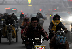 Citizens ride motorcycles amid heavy fog in Zhengzhou City, capital of central China's Henan Province, Jan. 16, 2013. Affected by a cold front, the haze which has lingered in most parts of Henan for the past two weeks will begin to disperse on Jan. 17, 2013, according to the meteorological authority, China, January 16, 2013. Photo by Imago / i-Images...UK ONLY
