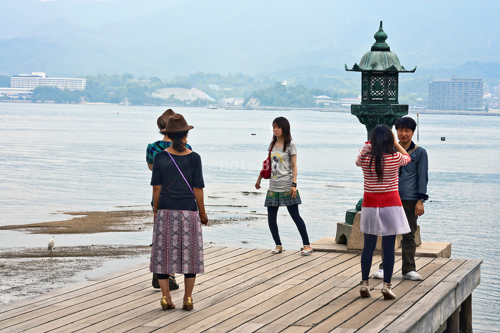 young adult Japanese tourist at the river in Itsukushima, Miyajima near the famous Torii gate, Japan