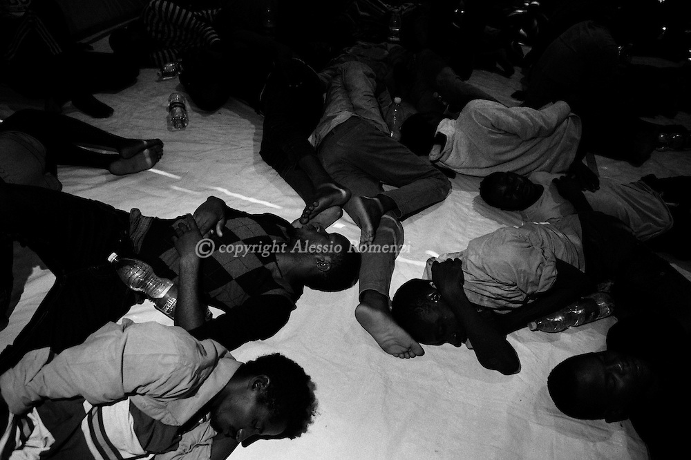 Italy,Southern Mediterranean sea: right after being rescued, African migrants exhausted by the journey on the sea rest on the deck of the Dignity1 (MSF boat) on August 31, 2015. Alessio Romenzi