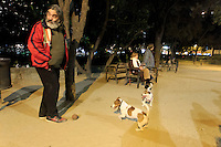 Every night in a small park opposite the Sagrada Familia, a group of dog owners gathers to let their small dogs play together away from larger dogs which may attack them. Barcelona, Spain.