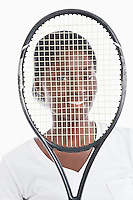Portrait of an African American young woman looking through tennis racket