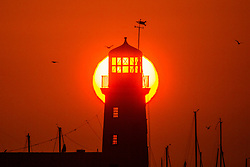 © Licensed to London News Pictures. 25/05/2020. Scarborough UK. The sun rises behind Scarborough lighthouse this morning on the Yorkshire coast. Photo credit: Andrew McCaren/LNP