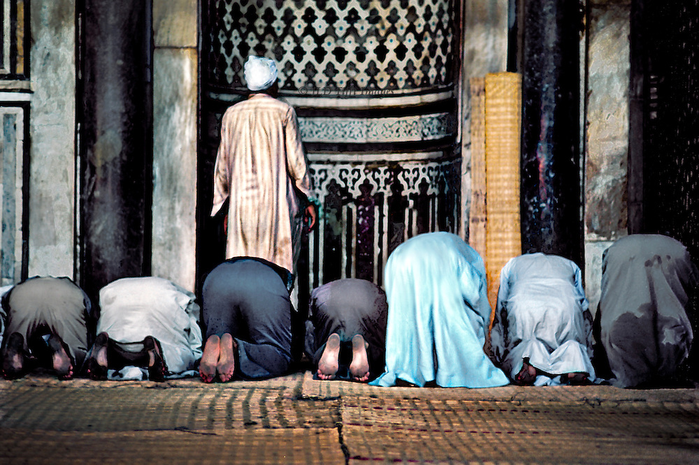 Worshippers at prayer in front of the qibla of the mostque of Sultan al Muayyad, near Bab Zuweila, Cairo, Egypt.  The Imam leading the prayers stands, while seven men kneel and bow behind him.  Some, including the Imam, wear galabeyyas, while others wear trousers. They are seen from behind.  The Qibla is ornamented with a design of colored tiles.  Straw matting on the floor.