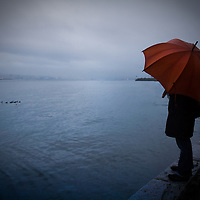 A woman standing on edge of water along seawall during a rainy day, holding an orange umbrella.