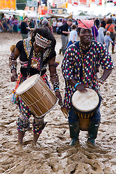 In spite of the muddy ground; festival goers make music at WOMAD (World of Music; Arts and Dance) Festival; Charlton Park; Malmesbury; 2007,