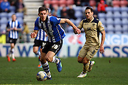 Jason Pearce of Wigan Athletic gets away from Billy Sharp of Leeds United. Skybet football league championship match , Wigan Athletic v Leeds Utd at the DW Stadium in Wigan, Lancs on Saturday 7th March 2014.<br /> pic by Chris Stading, Andrew Orchard sports photography.