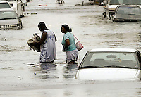 A man carries a baby through flood waters with a woman after they abandoned their car which started to float after Hurricane Katrina hit Terme area of New Orleans August 29, 2005. The White House said..Monday it was willing to use the government's emergency oil stockpile to help refiners hurt by Hurricane Katrina's rampage through the Gulf of Mexico, but that it was too early to decide if or how much crude should be released. The storm slammed into New Orleans on Monday with winds of..135 mph (216 kph), shutting 91 percent of the normal 1.5 million barrels per day of crude oil production in the Gulf Coast region.