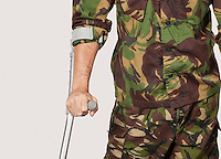 Mid section of young soldier holding crutches against gray background