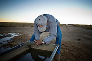 22 OCTOBER 2007 -- COYOTE CANYON, NM: MARK TSOSIE, 78 years old, a member of the Navajo Nation, fills a water tank on the back of his GMC pickup truck to haul water from a well to his home and his livestock. Tsosie has been hauling water all his life. He started working for the railroad when he was 14 years old. His job was to haul water to the workers. Now retired and he's still hauling water except now he hauls it to his home. More than 30 percent of the homes on the Navajo Nation, about the size of West Virginia and the largest Indian reservation in the US, don't have indoor plumbing or a regular supply of domestic water. Many of these homes have to either buy water from commercial vendors or haul water from public wells. A Federal study showed that the total cost of hauling water was about $113 per 1,000 gallons. A Phoenix household, in comparison, pays just $5 a month for up to 7,400 gallons of water. The lack of water on the reservation means the Navajo are among the most miserly users of water in the United States. Families that have to buy or haul water use only about 15 gallons of water per day per person. In Phoenix, by comparison, the average water use is about 170 gallons per day.  Photo by Jack Kurtz/ZUMA Press