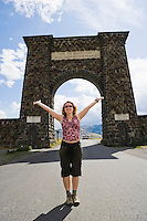 A happy woman standing in front of the North Entrance to Yellowstone National Park, Gardiner, Montana, USA.