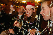 Three office friends wearing santa party hats celebrate Christmas with party streamers after work in the City of London.