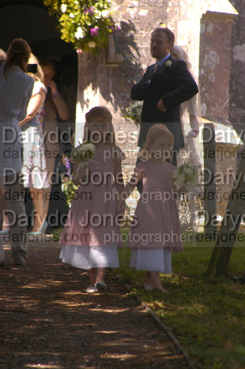 Molly Fox and Charlotte Gilmour. Marriage of Emilia Fox to Jared Harris. St. Michael's and All Angels. Steeple. Nr. Wareham. Dorset. 16 July 2005. ONE TIME USE ONLY - DO NOT ARCHIVE  © Copyright Photograph by Dafydd Jones 66 Stockwell Park Rd. London SW9 0DA Tel 020 7733 0108 www.dafjones.com
