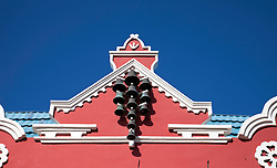 Aruba, Lesser Antilles.  Bells decorate the peak of a melon-colored building facade on Oranjestad's main street.  Ice cream-colors are a hallmark of the island's largest town, Oranjestad, usually within Dutch Colonial architectural design.