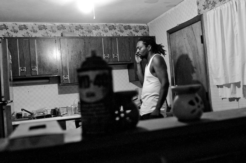"""Ryan speaks with his infant son's mother in his home in Gary, Indiana. Ryan's skill and love for golf has earned him the nom de guerre """"Tiger Hood."""" Ryan was recently let go in a round of layoffs from his job and is struggling to maintain mortgage payments on the home he purchased from his grandmother. (© William B. Plowman/Redux)"""