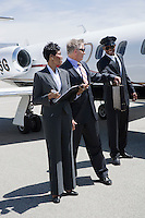 Senior businessman, mid-adult businesswoman and airline pilot in front of private jet.