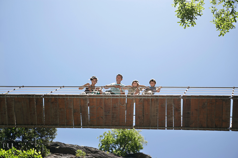 Parents and two sons (7-12) on bridge looking down