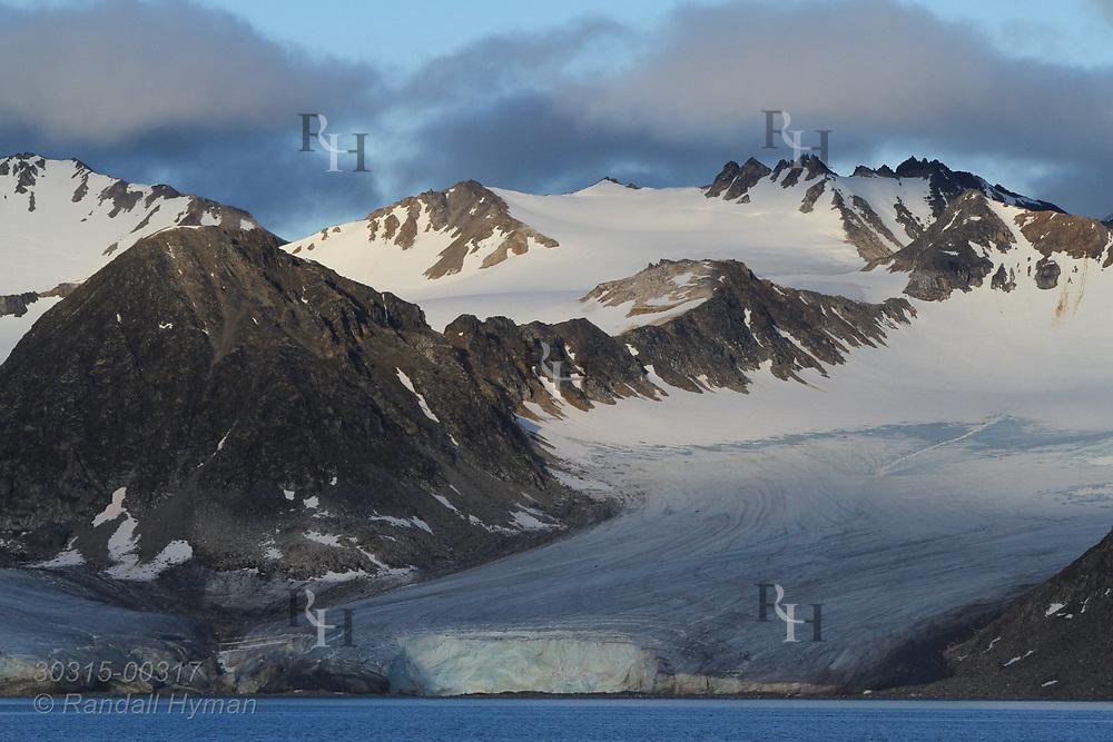 Glacier flows from mountains to sea in Smeerenburgfjorden on the north coast of Spitsbergen island; Svalbard, Norway.