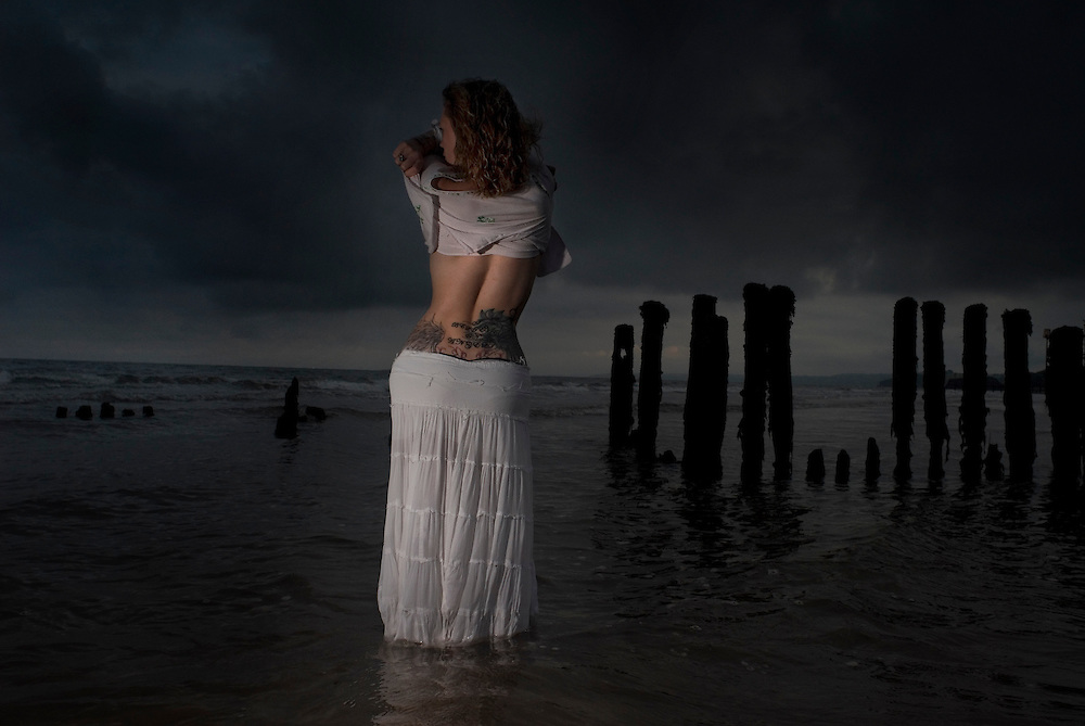 A statuesque girl in a white skirt and top stands in the sea at dusk, raising the top of her back to expose a large tattoo on her lower back.
