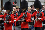 Guardsman, one black, march into position before the funeral of Margaret Thatcher. Draped in the union flag and mounted on a gun carriage, the coffin of ex-British Prime Minister Baroness Margaret Thatcher's coffin travels along Fleet Street towards St Paul's Cathedral in London, England. Afforded a ceremonial funeral with military honours, not seen since the death of Winston Churchill in 1965, family and 2,000 VIP guests (incl Queen Elizabeth) await her cortege.