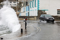 © Licensed to London News Pictures. 02/04/2018. St Austell, UK. A car narrowly avoids a large wave at Portmellon, Cornwall. Cornwall experienced heavy rainfall overnight, causing rough seas, flooding and road closures across the county. Photo credit : Tom Nicholson/LNP