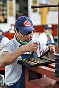 A cigarmaker called a torcedor places a bunch of cigars into a wooden mold which will then be pressed at the Santa Clara cigar factory in San Andres Tuxtlas, Veracruz, Mexico. The factory follows traditional hand rolling using the same process since 1967 and is considered by aficionados as some of the finest cigars in the world.