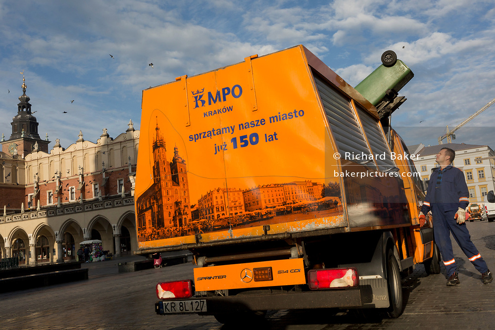 A wheelie bin empties trash into a city authority Mercedes Sprinter waste collection vehicle opposite the Renaissance Cloth Hall during morning rubbish duties on Rynek Glowny market square, on 23rd September 2019, in Krakow, Malopolska, Poland.