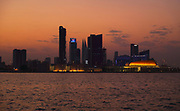 City skyline of Manama, the capital and largest city in Bahrain, at night. On the right is the National Theatre of Bahrain, opened 2012 and designed by Architecture-Studio. The theatre consists of a main 1001 seat auditorium and a smaller 150 seat flexible studio theatre. It is designed as a glass box offering views of the lagoon, with a golden overhanging roof providing shade. The city underwent much expansion in the 1980s and 1990s and is an important centre for the oil and financial industries. Picture by Manuel Cohen