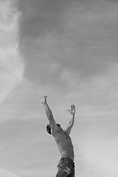 shirtless man reaching to the clouds