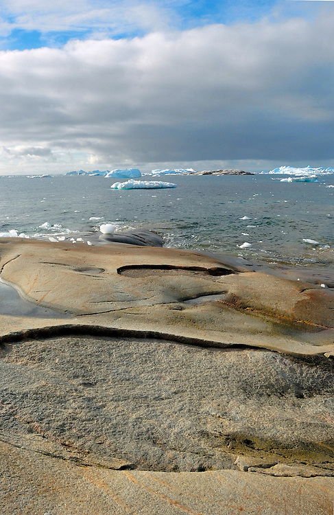 """Seascape of iceberg. Pieces of ice several cubic kilometres in size break offs and travels the Arctic sea, Greenland. Greenland (Greenlandic: Kalaallit Nunaat, meaning """"Land of the Kalaallit (Greenlanders) is a self-governing Danish province located between the Arctic and Atlantic Ocean. A recent study by researchers from NASA's Goddard Space Flight Center shows that Greenland's ice sheet, about 8% of the Earth's grounded ice, is losing ice mass."""