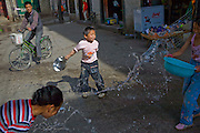 Children play with water outside their home in Lhasa, Tibet.