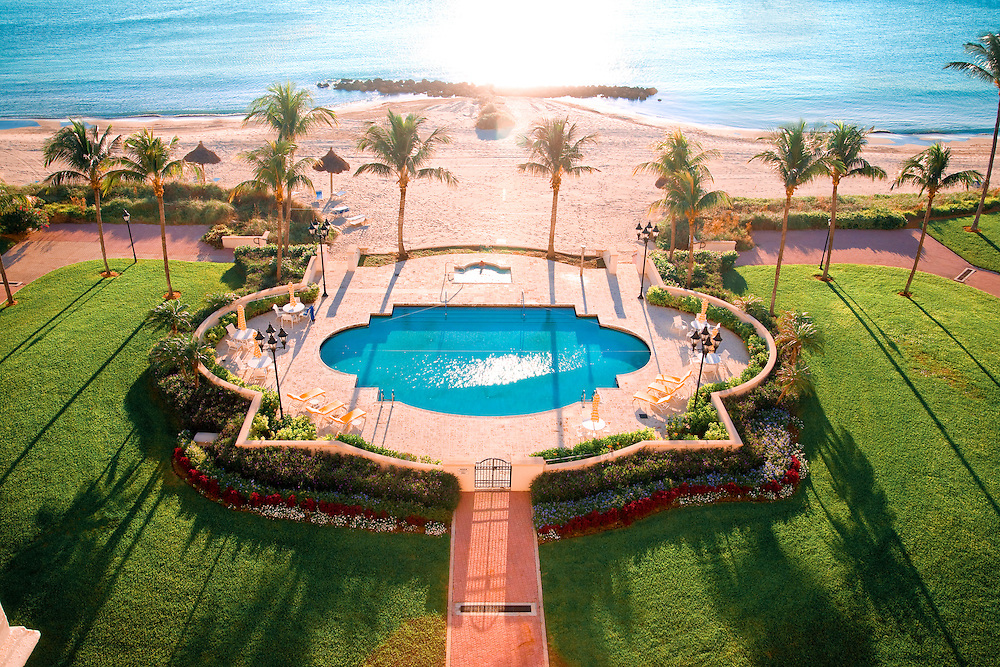 Early morning sunlight skims across a swimming pool on Florida's luxurious Fisher Island