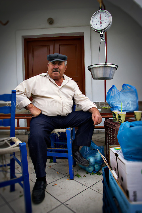 A man at a market in Santorini, Greece