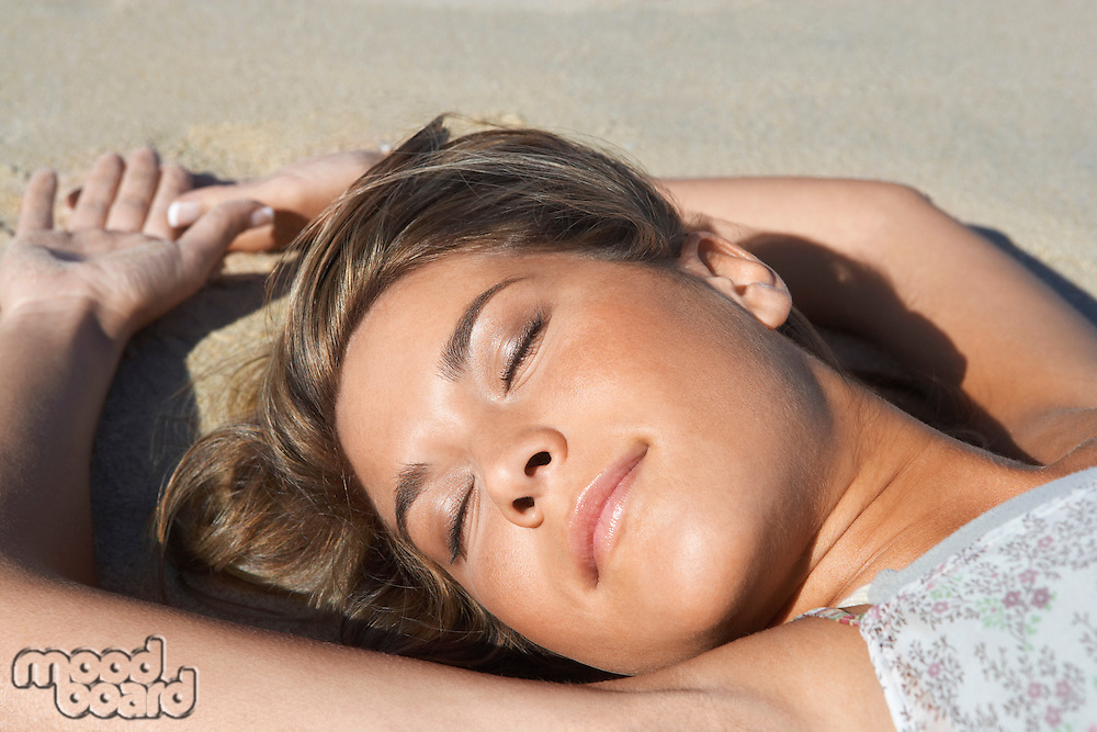 Young woman lying on beach close-up