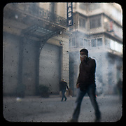 A man covering his nose and mouth walks on Ermou street while burned out shops still smoke. <br /> <br /> Following the murder of a 15 year old boy, Alexandros Grigoropoulos, by a policeman on 6 December 2008 widespread riots, protests and unrest followed lasting for several weeks and spreading beyond the capital and even overseas<br /> <br /> When I walked in the streets of my town the day after the riots I instantly forgot the image I had about Athens, that of a bustling, peaceful, energetic metropolis and in my mind came the old photographs from WWII, the civil war and the students uprising against the dictatorship. <br /> <br /> Thus I decided not to turn my digital camera straight to the destroyed buildings but to photograph through an old camera that worked as a filter, a barrier between me and the city.