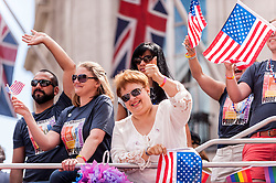 © Licensed to London News Pictures. 27/06/2015. Trafalgar Square, London, UK. Members of the US Embassy ride an open topped double-decker bus as they part in the annual Pride parade in London, one of the world's largest LGBT+ events.  Hundred of thousands of people gathered to watch the events on a hot summer's afternoon. Photo credit : Stephen Chung/LNP