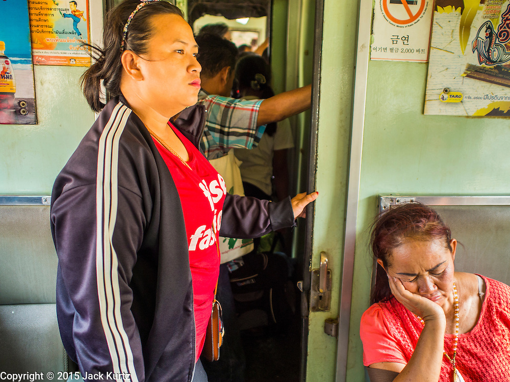 19 MARCH 2015 - AYUTTHAYA, AYUTTHAYA, THAILAND:  Passengers on the Ayutthaya to Bangkok third class train.  The train line from Bangkok to Ayutthaya was the first rail built in Thailand and was opened in 1892. The State Railways of Thailand (SRT), established in 1890, operates 4,043 kilometers of meter gauge track that reaches most parts of Thailand. Much of the track and many of the trains are poorly maintained and trains frequently run late. Accidents and mishaps are also commonplace. Successive governments, including the current military government, have promised to upgrade rail services. The military government has signed contracts with China to upgrade rail lines and bring high speed rail to Thailand. Japan has also expressed an interest in working on the Thai train system. Third class train travel is very inexpensive. Many lines are free for Thai citizens and even lines that aren't free are only a few Baht. Many third class tickets are under the equivalent of a dollar. Third class cars are not air-conditioned.   PHOTO BY JACK KURTZ