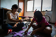 "31 MARCH 2013 - BANGKOK, THAILAND:     Nailintip ""Bang"" Cheunchum, 12, (RIGHT) helps Michelle Kao (LEFT) cut out crosses construction paper before Easter services at the Thai Peace Foundation office in the Bangkapi section of Bangkok.     PHOTO BY JACK KURTZ"
