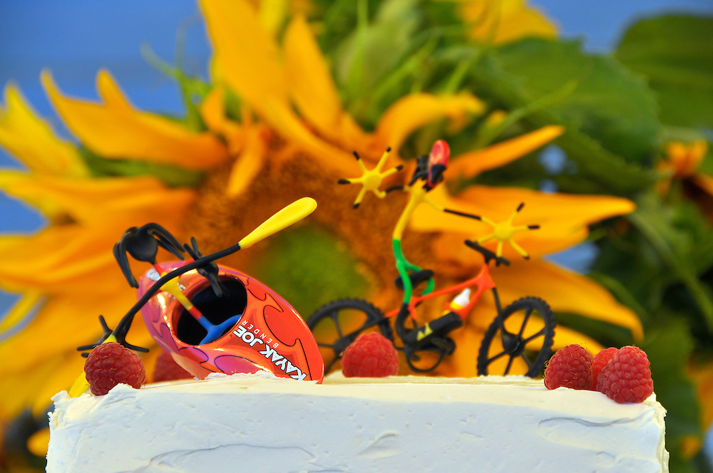 Wedding cake with flowers, raspberries and miniature kayaker and bicyclist.