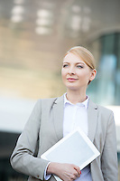 Confident businesswoman holding digital tablet outdoors