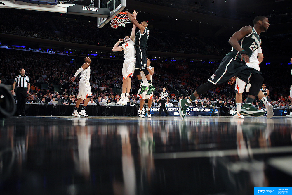 Adreian Payne, Michigan State, slams down a basket over Mike Tobey, Virginia, during the Virginia Cavaliers Vs Michigan State Spartans basketball game during the 2014 NCAA Division 1 Men's Basketball Championship, East Regional at Madison Square Garden, New York, USA. 28th March 2014. Photo Tim Clayton