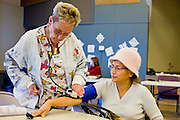 08 DECEMBER 2010 - PHOENIX, AZ:  MARY VON DWINGELO, a volunteer nurse with Mission of Mercy, takes the blood pressure of patient MARIA RUBIO at a Mission of Mercy mobile clinic in Phoenix, AZ, Wednesday, Dec. 8. Mission of Mercy has been providing free medical help for people in the Phoenix area since 1997. In the last two years, as the Arizona economy continued its recessionary slide, patient load at the clinics has more than doubled. Mission of Mercy, which relies on voluntary medical help and financial donations, recently acquired another mobile clinic so they could expand their reach into suburban areas they previously had not served. Mission of Mercy has provided free medical help to more than 43,000 patients in the Phoenix area since 1997.   PHOTO BY JACK KURTZ