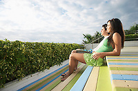 Teenage couple (16-17) sitting on wooden deck looking at view side view