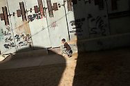 A young boy plays in a protected playground in Hebron's Jewish community. Some 600 Jews live in the heart of the old city surrounded by over 160,000 Palestinian inhabitants..Hebron, Israel. 01/11/2007.Photo © J.B. Russell/Blue Press